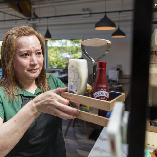 Woman putting condiments onto shelf